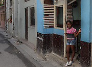 A young girl peaks out from a small cafe in Habana Vieja, Cuba.