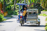 Locals take a ride aboard one of the many motorized tricycles that can be found  in PUERTO GALERA, the PHILIPPINES
