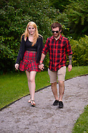 Old Westbury, New York, U.S. - August 23, 2014 - A young woman and man wearing red and black plaid outfits walk along a pebble path at the 54th Annual Long Island Scottish Festival and Highland Games, co-hosted by L. I. Scottish Clan MacDuff, at Old Westbury Gardens.