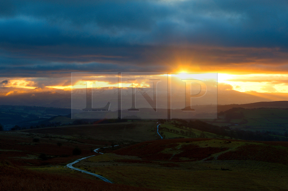 © Licensed to London News Pictures. 03/01/2017. Brecon, Powys, Wales, UK. The Mynydd Epynt moorland is seen in the foreground as the sunrises over the Brecon Beacons National Park on the horizon. A dusting of snow fell on 1st January on the higher peaks of the Beacons  above approximately 550 metres. The temperature last night in Mid Wales at 100 metres was approximately minus 1 degree centigrade. The moderate wind at 400 metres gave a 'feels like' temperature of about minus 4 degrees centigrade. Photo credit: Graham M. Lawrence/LNP