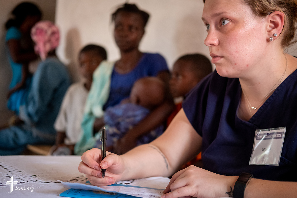 Lauren Awe, a nurse attending Beautiful Savior Lutheran Church, La Vista, Neb., listens to patients describe their maladies on the fourth day of the LCMS Mercy Medical Team on Thursday, May 10, 2018, in the Yardu village outside Koidu, Sierra Leone, West Africa. LCMS Communications/Erik M. Lunsford