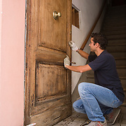 Man refinishing door to apartment, Siena, Tuscany, Italy<br />