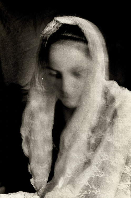 A young woman covering her head with a veil