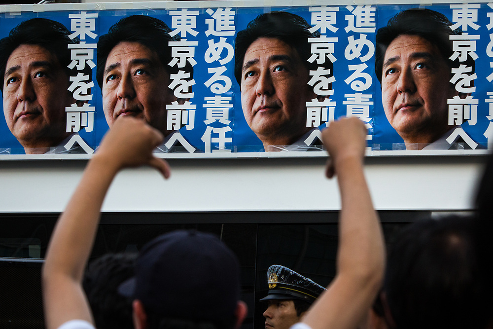 TOKYO, JAPAN - JULY 1: Japanese Prime Minister Shinzo Abe's campaign posters is seen from atop of a campaign van with anti-Abe protestor during election campaign for Tokyo Metropolitan Assembly on July 1, 2017 in Akihabara, Tokyo, Japan. (Photo: Richard Atrero de Guzman/NUR Photo)