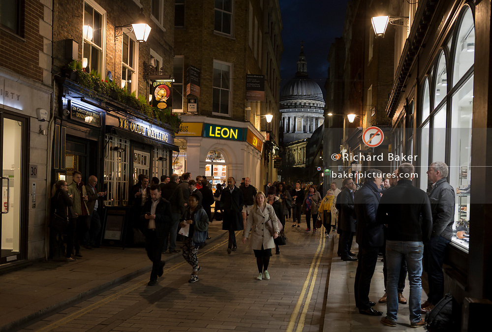 Evening crowds drink in the street with St. Paul's Cathedral in the distance, on the old Roman Watling Street, in the Square Mile, the heart of the capital's historical financial district, on 2nd October 2017, in the City of London, England.