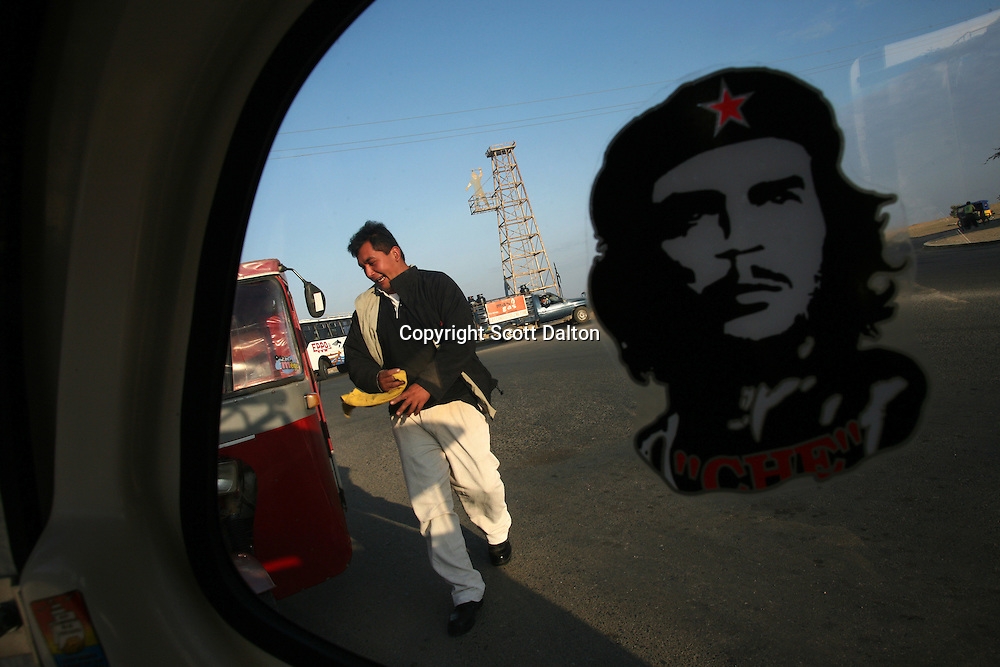 A motorbike taxi driver cleans his vehicle while waiting for customers near a monument to Talara's oil industry on November 9, 2007. Talara, located on Peru's northern coast, is Peru's main oil producing region and the Chinese company SAPET has an oil field in the region. (Photo/Scott Dalton)