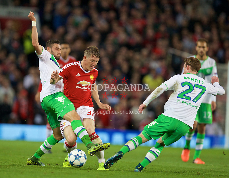 MANCHESTER, ENGLAND - Wednesday, September 30, 2015: Manchester United's Bastian Schweinsteiger is tackled by VfL Wolfsburg's Daniel Caligiuri and Maximilian Arnold during the UEFA Champions League Group B match at Old Trafford. (Pic by David Rawcliffe/Propaganda)