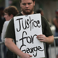 A George Zimmerman supporter holds a sign prior to the trial of George Zimmerman at the Seminole County Courthouse, Saturday, July 13, 2013, in Sanford, Florida. Zimmerman had been charged for the 2012 shooting death of Trayvon Martin, and was found not guilty by a jury of six women. (AP Photo/Alex Menendez)