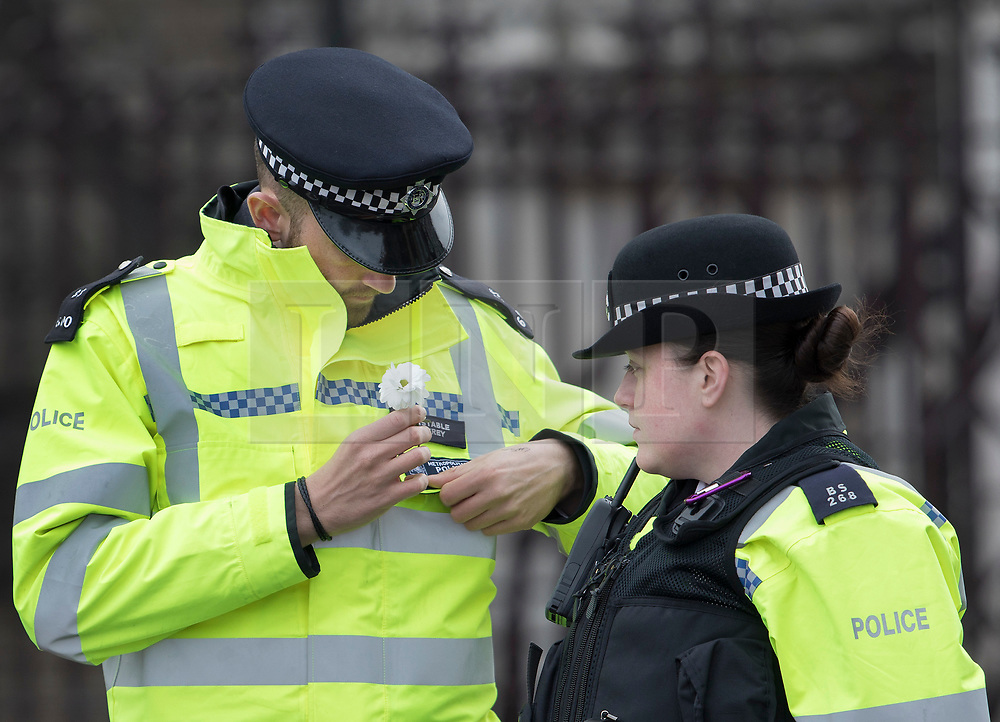 © Licensed to London News Pictures.23/03/2017.London, UK. A policeman fastens a flower onto his uniform in memory of his fallen comrade - as he mans a cordon on Westminster Bridge. A lone terrorist killed 4 people and injured several more, in an attack using a car and a knife at Parliament and on Westminster Bridge yesterday. The attacker managed to gain entry to the grounds of the Houses of Parliament, killing one police officer.Photo credit: Peter Macdiarmid/LNP