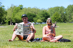 © Licensed to London News Pictures. 19/05/2020. London, UK. A man reads a copy of The Sun newspaper in Finsbury Park, north London on a warm and sunny day in the capital. The government has relaxed the rules on the COVID-19 lockdown, allowing people to spend more time outdoors whilst following social distancing guidelines. According to the Met Office, 27 degrees celsius is forecast for tomorrow. <br /> <br /> ***Permission Granted***<br /> <br /> Photo credit: Dinendra Haria/LNP