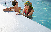 Two teenage girls (16-17) standing in swimming pool elevated view