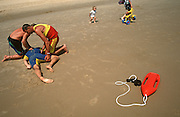 Lifeguards in the seaside resort of Lowestoft practise recover position and resuscitation to volunteer victim on beach.