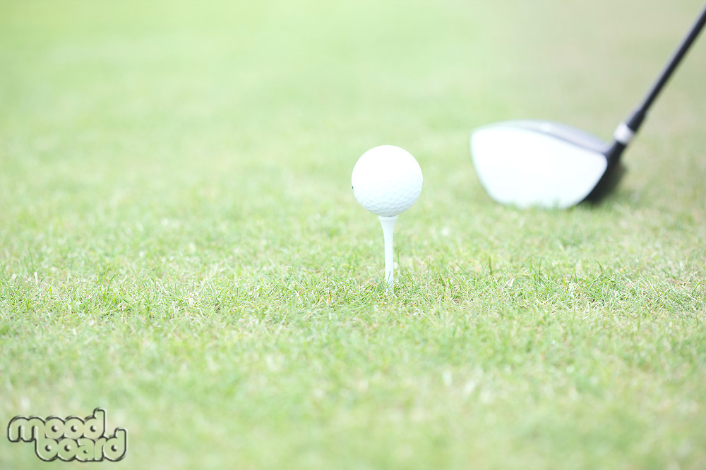 Close-up of golf club and tee with ball on grass