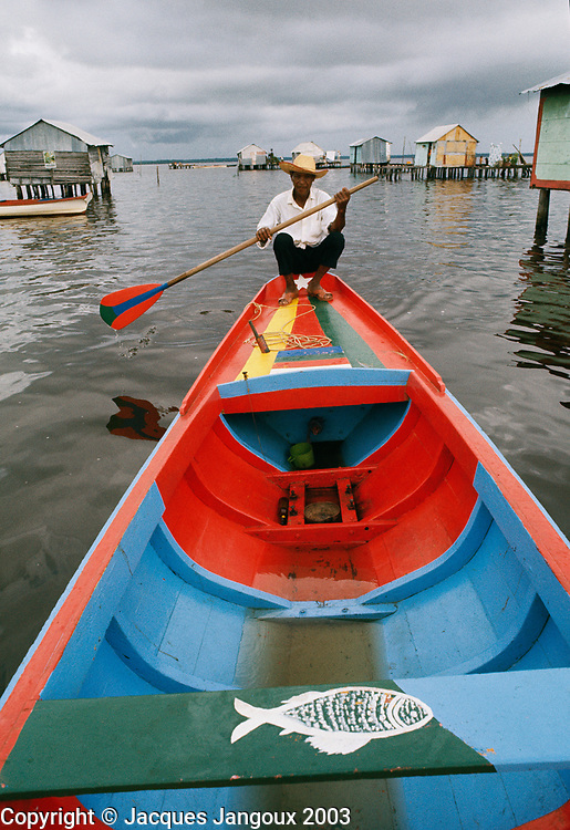 Dweller of stilt houses in Lake Maracaibo in Venezuela paddling, using his fishing boat for transportation.