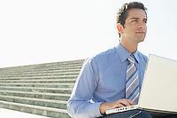 Young Business man sitting outdoors using laptop.