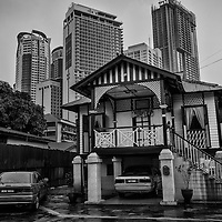 A traditional Malay architecture house stands against a modern skycrapers building in Kampung Baru, Malaysia.