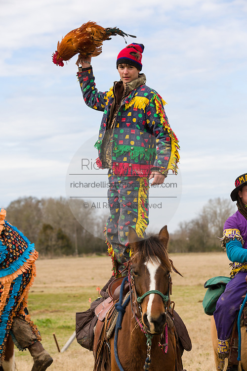 A costumed reveler stands on the back of their horse during the Mamou Courir de Mardi Gras chicken run on Fat Tuesday February 17, 2015 in Mamou, Louisiana. The traditional Cajun Mardi Gras involves costumed revelers competing to catch a live chicken as they move from house to house throughout the rural community.