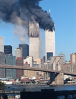 The World Trade Center moments after the South Tower was struck by United flight 175. Fire had not yet spread throughout the floors and debris can be seen falling along the north façade.