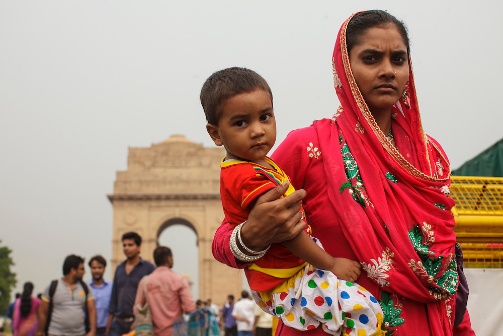 Mother and son near Delhi's India Gate arch, in India.