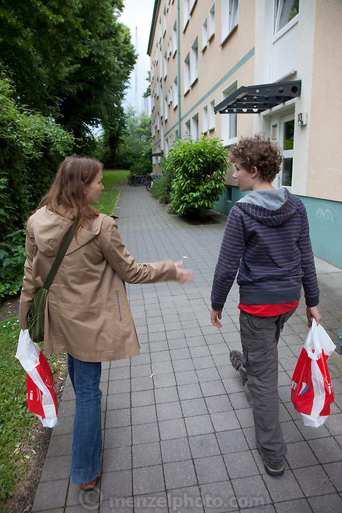 Astrid Holmann and her son Lenard in Hamburg, Germany returning to their apartment from shopping in the Aldi supermarket. They were photographed for the Hungry Planet: What I Eat project with a week's worth of food in June. Model Released.