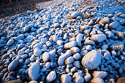 Fresh snow on cobble stones on the New Hampshire coast in Odiorne State Park in Rye, New Hampshire.  Winter.