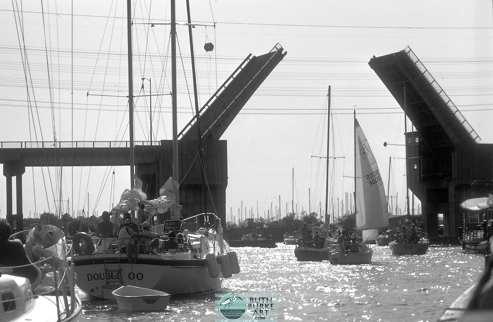 1980 Kemah and Seabrook Draw Bridge across the clear Creek Channel leading into Galveston Bay.  The bridge is open to let the sailboats pass.