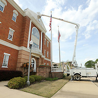 Donald Duffie, a Public Works Employee with the City of Tupelo, hovers high above the entrance of City Hall as he pressure washes the building at Fairpark in Tupelo Thursday. The washing is a regular maintenance item in keeping the building clean and the job will last a couple of days.