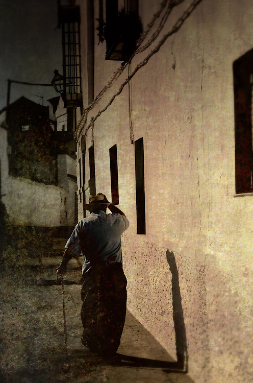 An old man wearing a straw hat walking with a stick along an old narrow street in a village in southern Spain