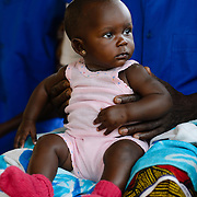 A baby in the arms of a traditional birth attendant in the village of Yapleu in western Cote d'Ivoire.