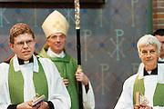 Na hun beëdiging luisteren de pastoors Bernd Wallet en Annemieke Duurkoop samen met de aartsbisschop Joris Vercammen naar een toespraak. Op zondag 31 oktober is in de Getrudiskathedraal in Utrecht  Annemieke Duurkoop als eerste vrouwelijke plebaan van Nederland geïnstalleerd. Duurkoop wordt de nieuwe pastoor van de Utrechtse parochie van de Oud-Katholieke Kerk (OKK), deze kerk heeft geen band met het Vaticaan. Een plebaan is een pastoor van een kathedrale kerk, die eindverantwoordelijk is voor een parochie. Eerder waren bij de OKK al twee vrouwelijk priesters geïnstalleerd, maar die zijn geen plebaan.<br /> <br /> Pastor Bernd Wallet (left) and dean Annemieke Duurkoop (right) are listening to words spoken to them. At the St Getrudiscathedral in Utrecht the first female dean of the Old-Catholic Church (OKK), Annemieke Duurkoop, is installed together with a new pastor Bernd Wallet. The church has no connections with the Vatican.