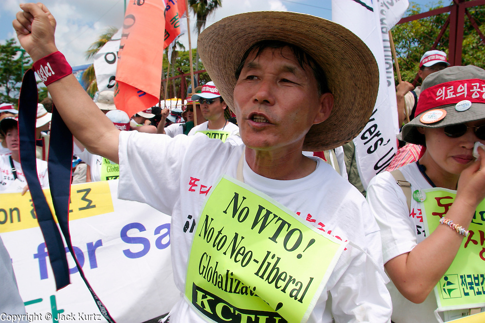 10 SEPTEMBER 2003 - CANCUN, QUINTANA ROO, MEXICO: Korean anti-globalization protestors march along the barricade separating the downtown area from the hotel zone in Cancun, Quintana Roo, Mexico during a protest against the WTO Wednesday. Lee Kyung-hae, one of the Korean protestors killed himself during the protest when he stabbed himself in the chest and then fell or jumped from a nearby rooftop. Tens of thousands of people opposed to the WTO have come to this Mexican resort city to protest the 5th Ministerial meeting of the World Trade Organization. The WTO meetings are taking place in the hotel zone of Cancun, about 10 miles from the protestors.  PHOTO BY JACK KURTZ