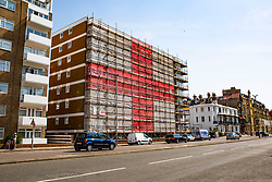© Licensed to London News Pictures. 01/07/2016. Brighton, UK. A 8 storey tower block in Brighton and Hove is covered in a giant England flag in support of the England Team at the World Cup. Steve Eason and his team took a week to cover the whole building in Hove on St Catherine's Terrace in Hove. Photo credit: Hugo Michiels/LNP