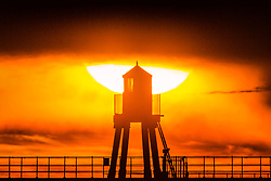 © Licensed to London News Pictures. 26/04/2019. Whitby UK. The sun rises behind the lighthouse at the end of Whitby pier at sunrise this morning on the Yorkshire coast. Photo credit: Andrew McCaren/LNP