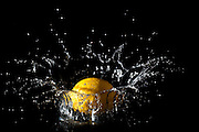 Action photograph of a Lemon splashing into water. Image has a black background and has a water splash frozen in the frame.