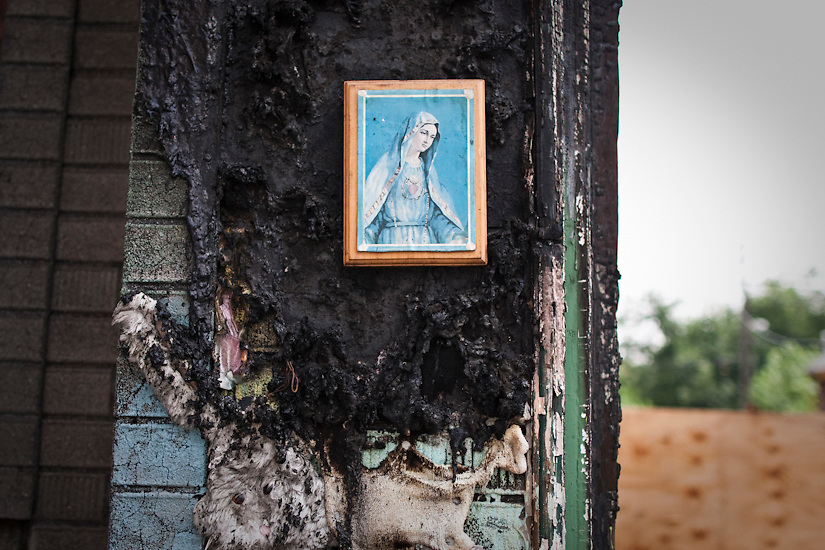 August 5, 2012 A portrait of the Virgin Mary hangs on the outside wall of a burned-out home in Detroit, MI.