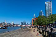 People enjoy the sun on the beach which appears every tide on the southbank of the River Thames. The easing of the 'lockdown' continues for the Coronavirus (Covid 19) outbreak in London.