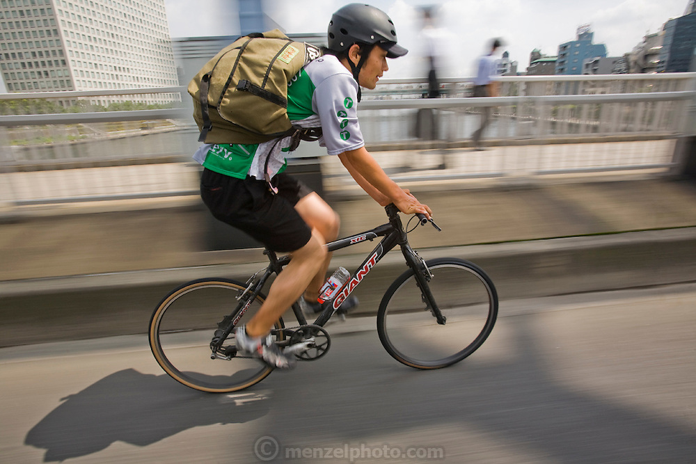 Jun Yajima, a messenger at T-Serv Bike Messenger service, rides across a bridge over the Tokyo River to make a delivery on the busy streets of Tokyo, Japan.  (From the book What I Eat: Around the World in 80 Diets.) MODEL RELEASED.
