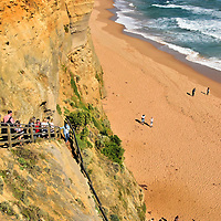 Descending Gibson Steps near Port Campbell on Great Ocean Road, Australia<br /> Get ready for a visual and physical adventure, your first inside of Port Campbell National Park. From an elevated platform near the Gibson Steps parking lot, you can admire the seascape embracing two rock stacks called Gog and Magog. Then begin descending this steep staircase. The 86 steps were first carved by the Kirrae Whurrong people. They were named after Scotland native Hugh Hamilton Gibson. He was an early settler who built the nearby Glenample Homestead in the late 1860s. He became famous in 1878 by sheltering the only two survivors of the 54 people who were shipwrecked aboard the British clipper Loch Ard.