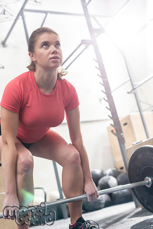 Confident woman lifting barbell in crossfit gym