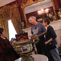 Emily Seymer, left, explains some of her collections to a couple from Atlanta in the parlor of her home, Holliday Haven.