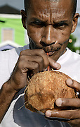 Jamaican man enjoys a coconut water jelly, Negril, Jamaica