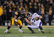 October 15, 2011: Northwestern Wildcats quarterback Dan Persa (7) falls towards Iowa Hawkeyes defensive back Tanner Miller (5) during the first half of the NCAA football game between the Northwestern Wildcats and the Iowa Hawkeyes at Kinnick Stadium in Iowa City, Iowa on Saturday, October 15, 2011. Iowa defeated Northwestern 41-31.