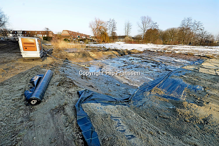 Nederland, Nijmegen, 26-1-2017Vijvers in de nijmeegse wijken Lindenholt en Dukenburg dreigen overwoekerd te raken door een exotische aquariumplant. Een vijver is leeggehaald en de bodem afgedekt met watterdoorlatend plastic. Een naastliggende vijver blijft een jaar lang leeg en de bodem overdekt met plastic. Hiermee hoopt de gemeente de woekerende waterplant definitief weg te krijgen. Het gaat om de Watercrassula, een exoot uit Australie. Salamanders en kikkers worden gevangen en overgeplaatst naar andere vijvers.Foto: Flip Franssen