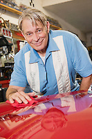 Smiling elderly man cleaning red hood of car in automobile repair shop