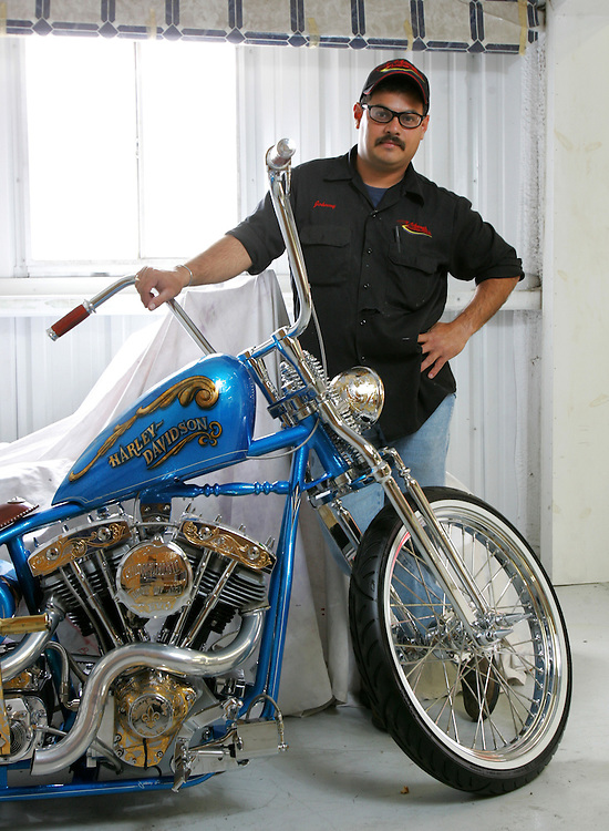 Photo by Alex Jones..Johnny Gil, owner of Johnny's Custom Shop, poses with a Harley-Davidson featuring 28k gold leaf inlays.