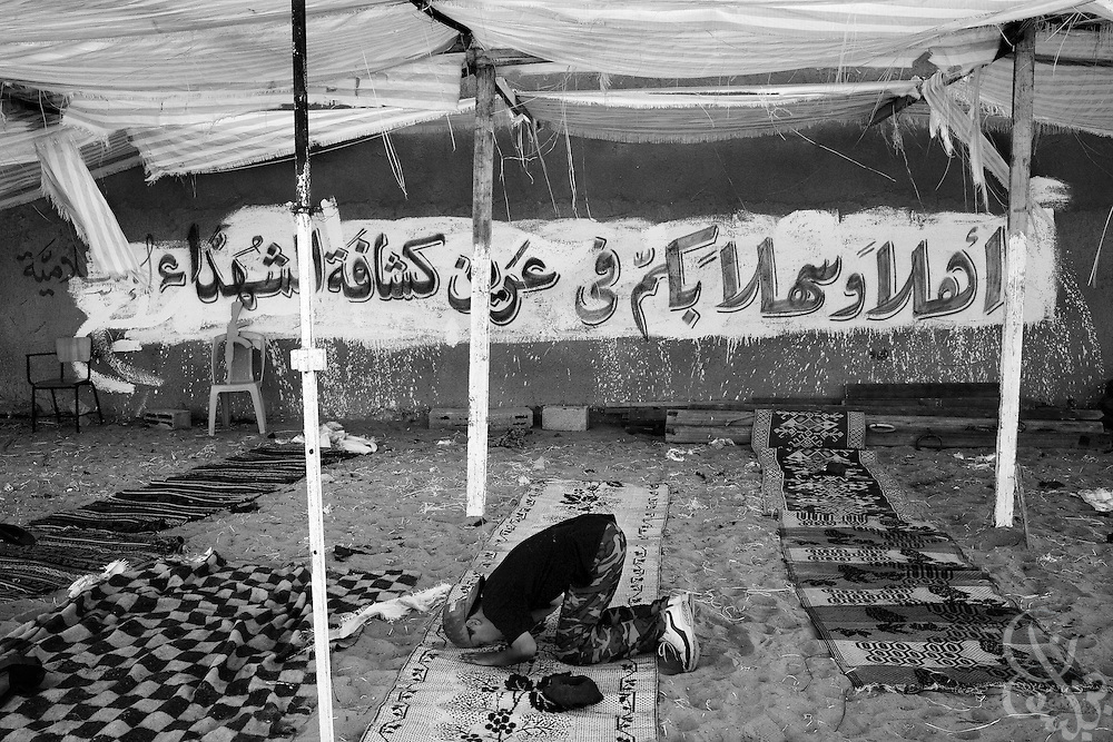 "A Palestinian boy prays under a sign that reads ""Welcome to the den of the martyr campers!""  August 05, 2007 at a HAMAS sponsored summer camp in the Nuseirat camp in the Gaza strip. Kids at the camp are given military style training 6 days a week at the camp for 3 hours per day."