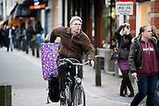Een man fietst met een groot cadeau voor Sinterklaas op de fiets door de Zadelstraat in Utrecht