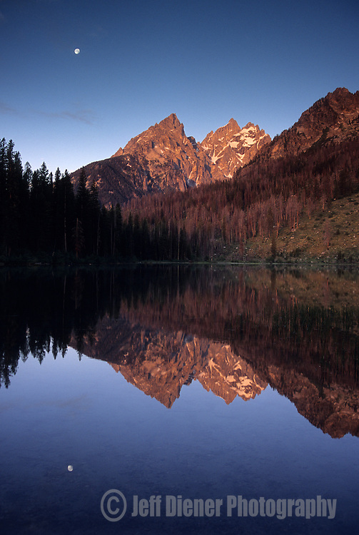 The high peaks of the Tetons and a full moon are reflected in String Lake, Grand Teton National Park, Wyoming.