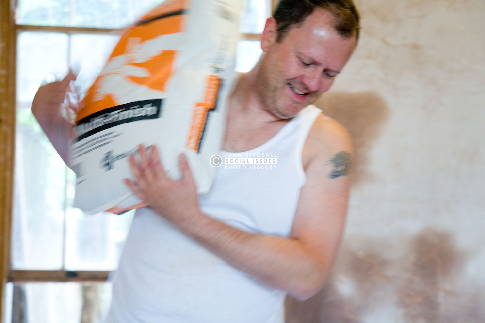 Man caring a bag of plaster,