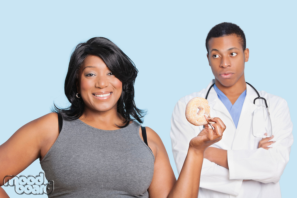 Overweight mixed race woman with donut by doctor over blue background